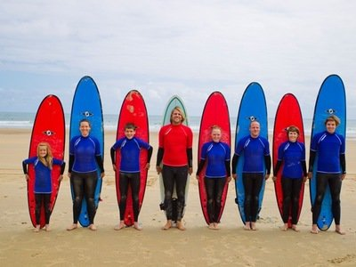 surfboards with surfers at the surf school in spain